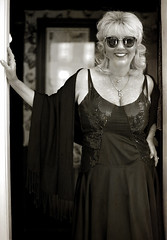 Dolly (Anthony Mark Images) Tags: people female portrait dollyshouse dolly blacksequindress prettylady blackshawl sunglasses brothel smile redlightdistrict blackandwhite goldchains sepia blondehair history nikon monochrome doorway soliciting prostitute d850 actress voluptuous lovely prettywoman beautiful