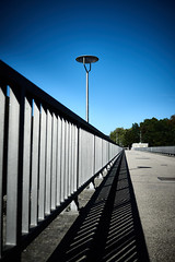 Bridge. Balustrade. Blue. (iamunclefester) Tags: münchen munich asatouristinmyhometown street bridge balustrade lamp lantern light sky blue trees perspective lines vanishing point vanishingpoint castshadow hardshadow shadow kabelsteg manualfocusday manualfocus