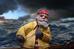 The Fisherman And The Sea (Anthony Mark Images) Tags: art woodcarving sculpture handpainted fisherman sea waves clouds rough ocean boat nets rope yellowraincoat redtouque greyhair beard bushyeyebrows gloves redwhitestripes seattle washington usa nikon d850