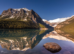 Lake Louise First Sunlight (Paul Berkloo) Tags: lakelouise alberta canada ca water lake calm mountain mountains mountainside rock rocks cliff snow ice reflection reflections landscape sky tree
