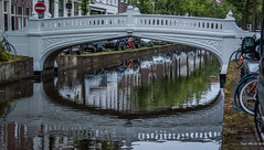 2018 - Delft - Canal Bridge (Ted's photos - For Me & You) Tags: 2018 cropped delft nikon nikond750 nikonfx tedmcgrath tedsphotos vignetting delftcanal reflection waterreflection bridge arch bicycles bikes red redrule