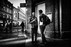 Just gesticulating (Kieron Ellis) Tags: people man men standing streetcorner corner wall pavement signs street candid blackandwhite blackwhite monochrome