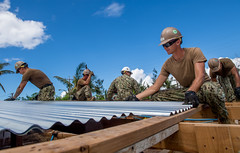 Seabees apply metal roofing sheets while reconstructing.