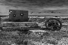 Things Left Behind (24) (Dungeness)-03280 (G.K.Jnr.) Tags: landscape seascape foliage vegetation historic cog machinery gearwheel deserted desolate discarded dilapidation concrete wood metal sea seaside coastline beach shingle outdoor sky scenic interest touristattraction monochrome bw blackandwhite blackwhitephotos rural dungeness romneymarsh kent unitedkingdom fujix apsc xh1