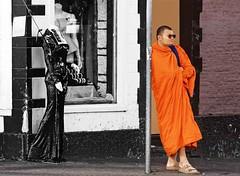 Twee werelden in een notendop (Roel Wijnants) Tags: ccbync roelwijnants roelwijnantsfotografie roel1943 thaisemonnik thaise monnik glitterglamour glitter glamour kleding jurk tweewerelden geloof levenswijze overtuiging kleur oranje sangha straatfoto bw shop dress sandalen eenvoud nutshell
