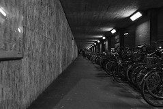 Underpass of Bikes  (FIlm) (Harald Philipp) Tags: geometric bridge underpass structure urban citycenter sidewalk pavement city town street people atmosphere haraldphilipp night bicycles bikes blackandwhite bw blackwhite monochrome schwarzweiss nocolor dark shadows contrast fujisuperia 35mm film grain analog filmphotography primelens nikon nikkor europe european switzerland schweiz zug moody
