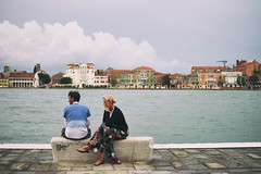Being in the Same Direction (Marta Marcato) Tags: venice venezia couple love water building panorama street streetphotography man woman italy italia travel laugh blue buildings lagoon clouds smile happy happiness looking