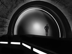 alone in nowhere (heinzkren) Tags: schwarzweis blackandwhite bw sw monochrome fantasy man light magical mystery walk composing solo escalator rolltreppe architecture silhouette lines curves abstract panasonic lumix