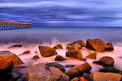 Rocking at dusk (Fnikos) Tags: sea water waterfront mar mare wave seascape landscape pont puente pier bridge architecture construction rock sand coast beach shore seashore dusk nightfall anochecer sky skyline light cloud outdoor