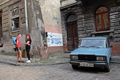 LVIV - COUPLE WITH CAR (Maikel L.) Tags: europa europe ukraina ukraine украина україна львов львів lviv lwiw lwów lvov lemberg street streetlife streetscene couple paar man mann guy woman frau begegnung encounter car lada vintagecar streetcorner rincon gespräch dialogue rot red
