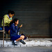 Two girls doing their hair before school outside Warorot Market in Chiang Mai, Thailand
