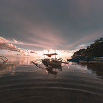 Sunset peaking behind a pumpboat in Sipalay thumbnail