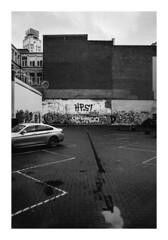 161120_00001_OM2n_city fragment 14/20 (A Is To B As B Is To C) Tags: aistobasbistoc b belgië belgium antwerpen antwerp meir gramayestraat boerentoren olympus om2n analog film bw blackwhite blackandwhite monochrome parking parkinglot car city cityscape wall graffiti tag tags rain water reflection sky clouds cloudy urban tower kbc skyscraper fragment