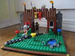 At the Gateway (jgiese626) Tags: lego moc vignette knight spearman crossbowman peasant boy dragon lion archway gate gateway castle fort wall battlements torch shrubs shrubbery foilage grass flowers pond path frog