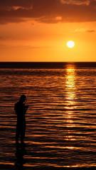 Man prepares his fishing rod in the sunset (b.kuehweidner) Tags: sonnenuntergang meer wasser himmel ozean mauritius strand beach heaven water ocean sunset