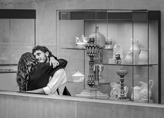 Ecstacy in Ceramics (John St John Photography) Tags: metmuseum metropolitanmuseumofart fifthavenue newyorkcity newyork streetphotography candidphotography theamericanwing lovers manandwoman embrace hug display cases ceramics bw blackandwhite blackwhite blackwhitephotos johnstjohnphotography