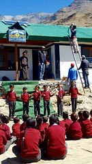 Students perform a special dance while the GHE team installs a street light on the roof at Skiagam school