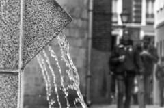 La fuente de la plaza (Lea Ruiz Donoso) Tags: madrid comunidaddemadrid españa es spain calledelbiombo calles streetscenes street plaza fuente fountain caños agua centro ciudad bokeh people gente bw byn blancoynegro sony monocromo dof