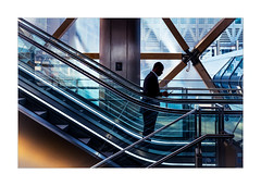 In the space station (Dave Fieldhouse Photography) Tags: streetphotography street canarywharf escalator man phone mobilephone london city citycentre interior architecture modernarchitecture building offices people fujixpro2 fujinon35mmf2 fuji fujifilm wwwdavefieldhousephotographycom project sillouette