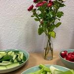 Holztisch mit grünen Tellern mit geschnittenem Gemüse wie Gurken, Sellerie und Radieschen, in der Mitte eine transparente Vase mit roten und weißen Blumen vor weißer Wand thumbnail