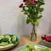 Holztisch mit grünen Tellern mit geschnittenem Gemüse wie Gurken, Sellerie und Radieschen, in der Mitte eine transparente Vase mit roten und weißen Blumen vor weißer Wand