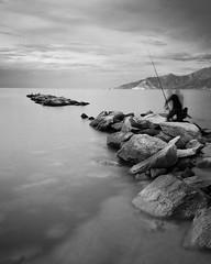 The Fisherman (Wilco1954) Tags: cormorant baiedesaintflorent mono fsherman rockypier longexposure stillness sea