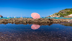 Double umbrella (Nicola Pezzoli) Tags: menorca baleares baleari island nature spain sea minorca isola cala algaierens umbrella reflections water red blue beach vivid