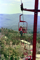 71-036 (ndpa / s. lundeen, archivist) Tags: nick dewolf nickdewolf color photographbynickdewolf 1975 1970s film 35mm 71 reel71 hanggliding hangglidingfestival lift skilift chairlift man youngman gear equipment helmet building shed sunglasses shades franconia franconianotch newhampshire newengland mittersillalpineresort mittersill cannon mountain whitemountains worldcup competition hangglidingcompetition summer worldcupmeet meet mittersillworldcupmeet july