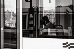 surrounded by reflections (Gerard Koopen) Tags: nederland netherlands amsterdam capital city reflections man traveling tram publictransport gvb music listening straat street straatfotografie streetphotography streetlife bw blackandwhite blackandwhiteonly sony sonyalpha a7iii 2018 gerard koopen gerardkoopenphotography