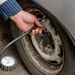 Man checking air pressure and filling air in the tires of his car thumbnail