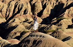 Mound With A View (Harald Philipp) Tags: woman hat whitedress cowboyboots blondehair geology geologicalformation solitude holiday vacation tourism tourist exotic destination travel adventure wanderlust beautiful romantic serenity dreamy enchanting haraldphilipp outdoors rural panorama scenic scenery landscape alien otherworldly light desolate desolation hill grass bushes volcanicash sand ancient historic natural artisticnature abstractreality shadows depthoffield nikon nikkor d810 unitedstates northamerica usa park nationalpark western westernusa badlands erosion