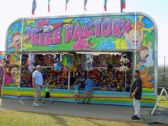 Prize Factory Balloon Darts. (dccradio) Tags: lumberton nc northcarolina robesoncounty outdoor outdoors outside sky clouds robesonregionalagriculturalfair fair countyfair robesoncountyfair fun entertainment communityevent bigrockamusements carnival midway prizefactory balloon balloons balloondarts bust1wins shadow flag flags people sign words text paved pavement walkway grass lawn greenery yard ground plush prizes nikon coolpix l340 bridgecamera