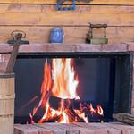 Kaminfeuer umrahmt mit Backsteinen und antiken Objekten thumbnail
