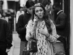Lost for Words (Stuart Mac) Tags: candid street phone surprise beauty face expression london 85mm nikon scarf shopping portrait