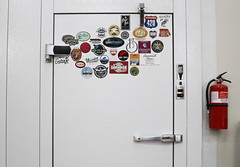 All kinds of stickers are placed on  the outside of the freezer door including stickers from other breweries, such as Creature Comforts Brewing Co. located in Athens, Georgia.
