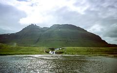 Kirkjufellsfoss (hiphopmilk) Tags: copyright©jaredyehwooehmoehfilms nikonfm2n nikonfm2 nikon fm2 35mm 135film film analog analogue kodak nikkor hiphopmilk north europe nordic iceland kirkjufell kirkjufellsfoss waterfall mountain snæfellsnes grundarfjörður church water sunshine cloud sky