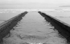 Canal (Manuel Goncalves) Tags: canal sea ocean santos brazil beach water blackandwhite 35mmfilm addox100 pentaxme epsonv500scanner 50mmlens monochrome