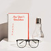 New year's resolution. Desk with notebook, glasses and decorative lamp. White background.